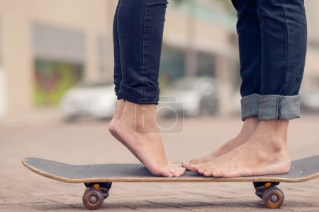 Photo for Cropped image of a young couple standing on the skateboard outside - Royalty Free Image