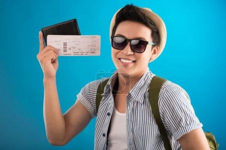 Photo pour Image isolée d'un jeune homme heureux avec des billets entre les mains sur un fond bleu - image libre de droit