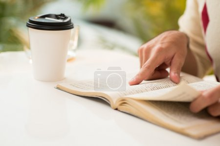 Photo for Cropped image of a person reading in the morning while drinking espresso coffee on the foreground - Royalty Free Image