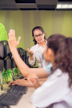 Photo pour Verticale de l'image d'un enseignant demandant à ses élèves de répondre alors que l'un d'entre eux à mettre en place ses mains sur le premier plan - image libre de droit