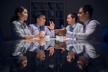Foto de Imagen de un grupo de empresarios discutiendo el plan de negocios emocionalmente antes del plazo durante la noche - Imagen libre de derechos