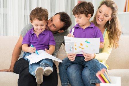 Photo pour Parents joyeux dessin avec leurs enfants à la maison - image libre de droit