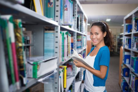 Photo pour Adolescente à la recherche d'un livre dans la bibliothèque - image libre de droit