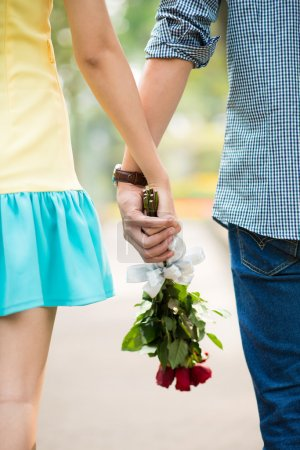 Photo for Close-up of clutched hands of two lovers with bouquet - Royalty Free Image