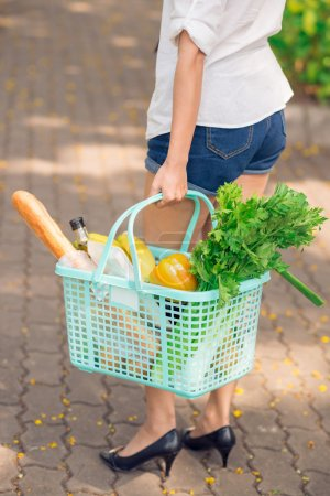 Photo for Cropped vertical image of a woman with a shopping basket full of food products - Royalty Free Image