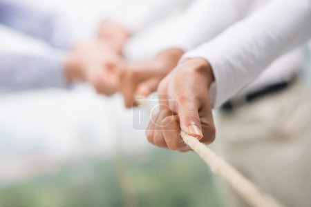 Photo for Concept image of business team using a rope as an element of the teamwork on the foreground - Royalty Free Image