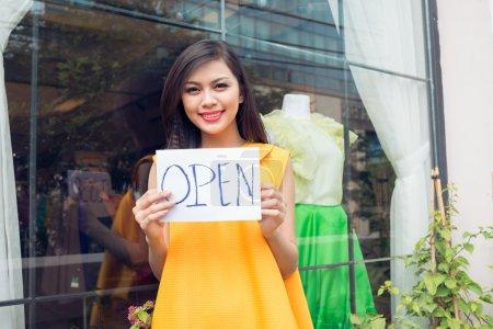 Photo pour Gros plan d'un charmant commerçant ouvrant la boutique au premier plan - image libre de droit