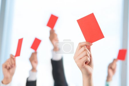 Hands showing red cards