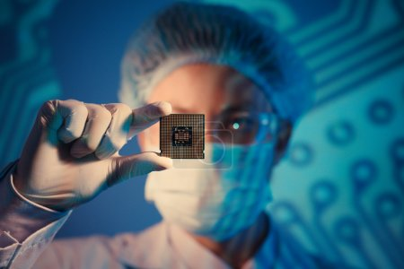 Photo for Computer engineer holding microchip for detailed analysis on the foreground - Royalty Free Image