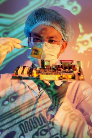 Photo for Vertical image of a concentrated it-engineer holding computer chip with tweezers on the foreground - Royalty Free Image