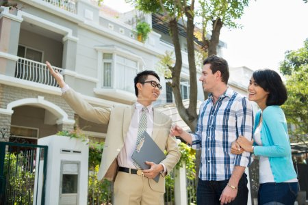 Photo for Estate agent showing a house to the young family - Royalty Free Image