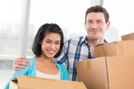 Photo pour Jeune couple souriant portant des boîtes en carton - image libre de droit