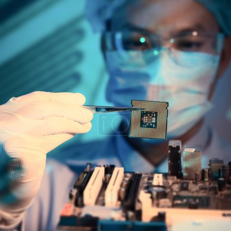 Photo for Close-up image of an it-engineer with chip holding in tweezers on the foreground - Royalty Free Image