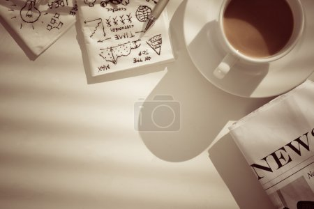 Photo for Coffee, newspaper and napkins with pictures, showing business breakfast - Royalty Free Image
