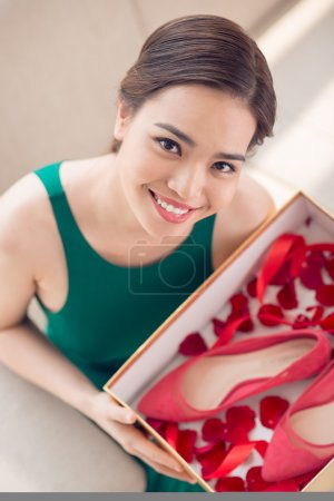 Photo for Young woman holding a box with red heels and rese petals, view from the top - Royalty Free Image