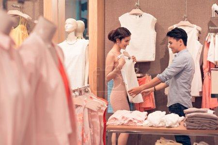 Photo pour Azjatyckie kobiety konsultacji ze swoim chłopakiem podczas przymierzania bluzka - image libre de droit