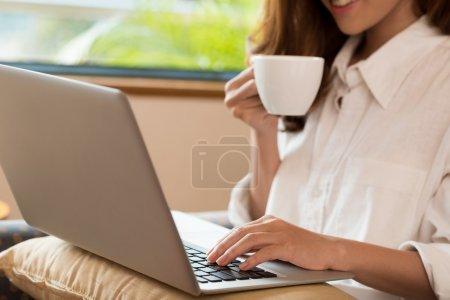Photo pour Gros plan de femme boire du café tout en utilisant l'ordinateur portable - image libre de droit