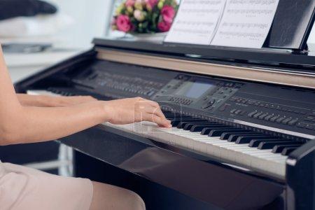 Photo pour Gros plan de la femme jouant du piano, du corps et des boutons du piano ont été modifiés numériquement - image libre de droit