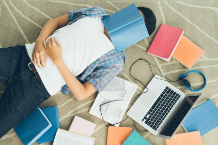 Photo for Exhausted student fall asleep with a textbook on his face - Royalty Free Image