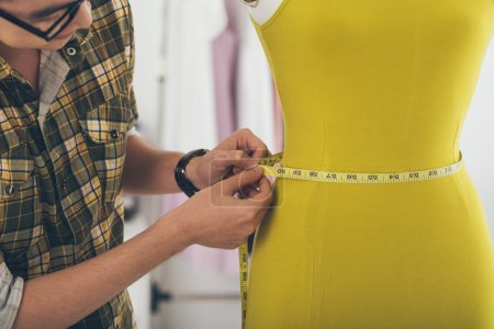 Photo for Male tailor measuring a waist of the mannequin - Royalty Free Image
