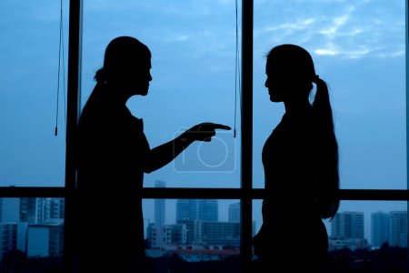 Photo for Silhouette of woman punishing her teenage daughter: generation conflict - Royalty Free Image