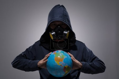 Man in respirator holding a globe