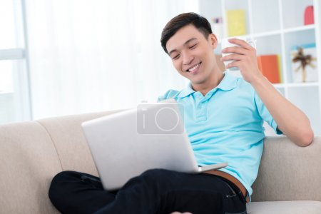 Photo for Smiling man sitting on the sofa and using laptop - Royalty Free Image