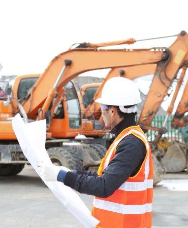 road construction worker in front of excavator