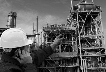 Photo pour Ingénieur appelant et pointant vers une grande raffinerie de pétrole en vue blac et blanc - image libre de droit