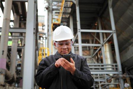 Photo pour Ingénieur raffinerie de pétrole communiquer via téléphone mobile - image libre de droit