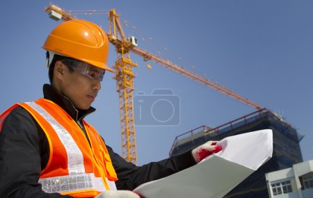Photo for Construction worker checking a blueprint with crane on the background - Royalty Free Image