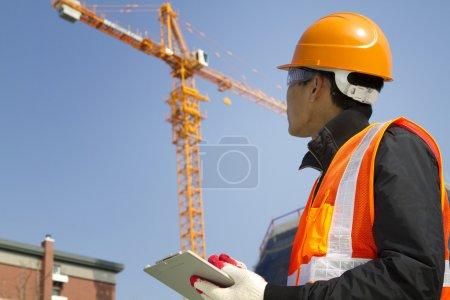 Photo pour Travailleur de la construction vérification emplacement avec grue sur le fond - image libre de droit
