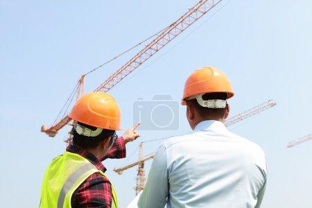 Photo pour Activité de travailleur Builder avec grues sur le fond - image libre de droit