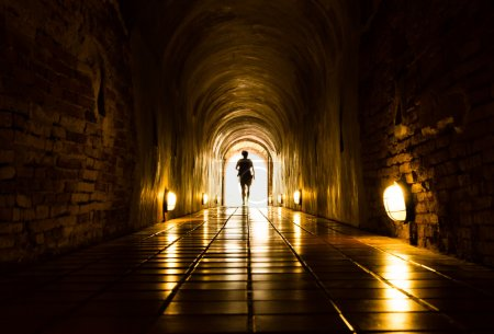 Photo for Silhouette of human in old brick tunnel light at end of tunnel - Royalty Free Image