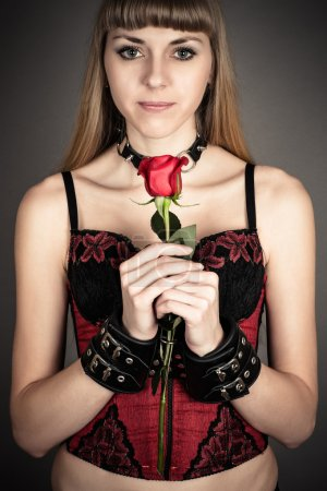Woman in handcuffs with a rose in hand