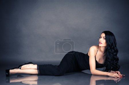 Photo pour Belle femme séduisante en robe noire couchée sur le sol - image libre de droit