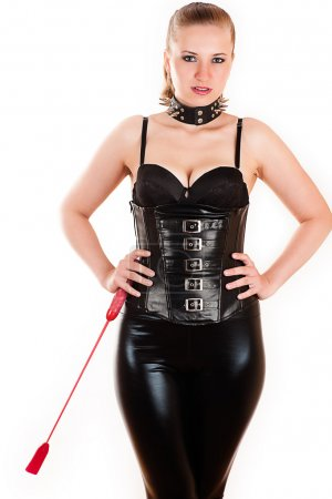 Beautiful woman in the image of mistress with whip