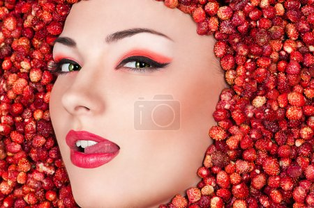 Photo for Fashion woman face licking lips lying in wild strawberry - Royalty Free Image