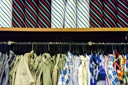 Photo for Colorful collection of men's clothes hanging on a rack and Colorful roll T-Shirts on the top layer. - Royalty Free Image