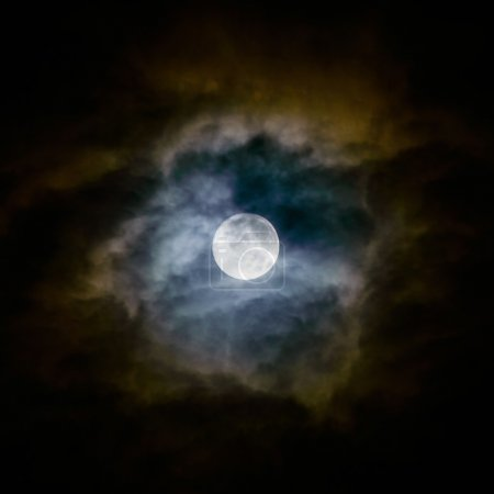 Full moon and clouds on night sky.