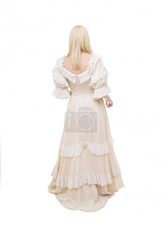 Photo for Beautiful Victorian Lady is walking in white background. View from back. Beige Dress with flowers, Ruffles and Lace. Long fair straight Hair. - Royalty Free Image