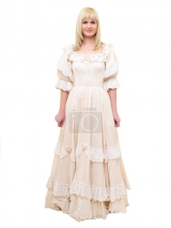 Photo for Beautiful Victorian Lady standing in white background. Beige Dress with flowers, Ruffles and Lace. Long fair straight Hair. Looking at the Camera. - Royalty Free Image