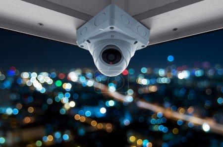 Photo pour De veiligheid camera's op een balkon hoog gebouw. uitzicht op de stad bij nacht met wazig licht - image libre de droit