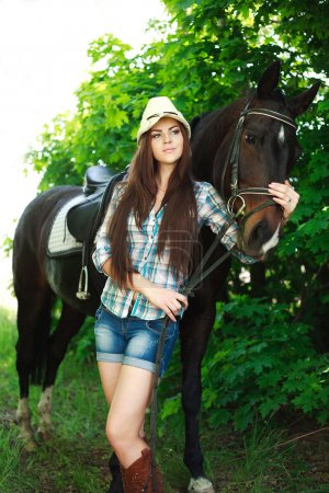 Outdoor portrait of beautiful cowgirl with horse in green