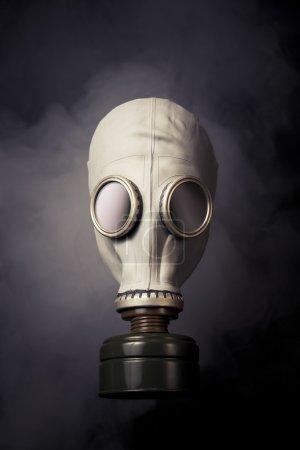 gas mask with smoke on a dark bakground