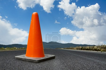 traffic cone on a road with a bright blue sky