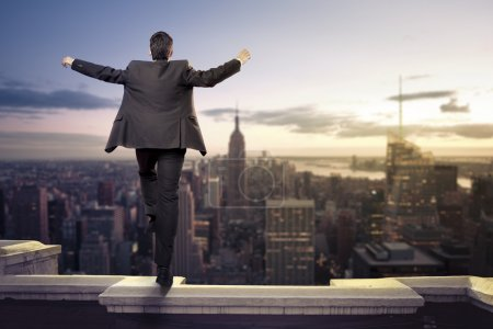businessman standing with open arms on top of NY city