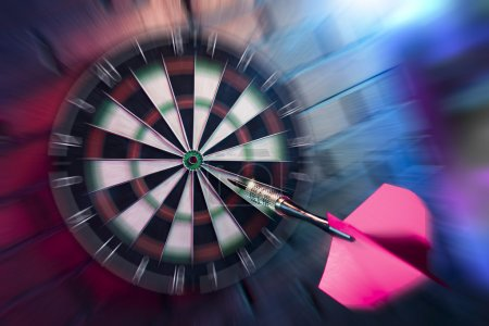 Photo for Dart about to hit target with dramatic lighting at dartboard - Royalty Free Image