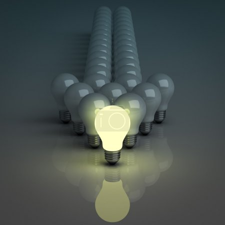 Photo for Leadership concept, One glowing light bulb standing in front of unlit incandescent bulbs with reflection on dark background - Royalty Free Image