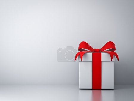 Gift box with red ribbon bow and empty white wall background